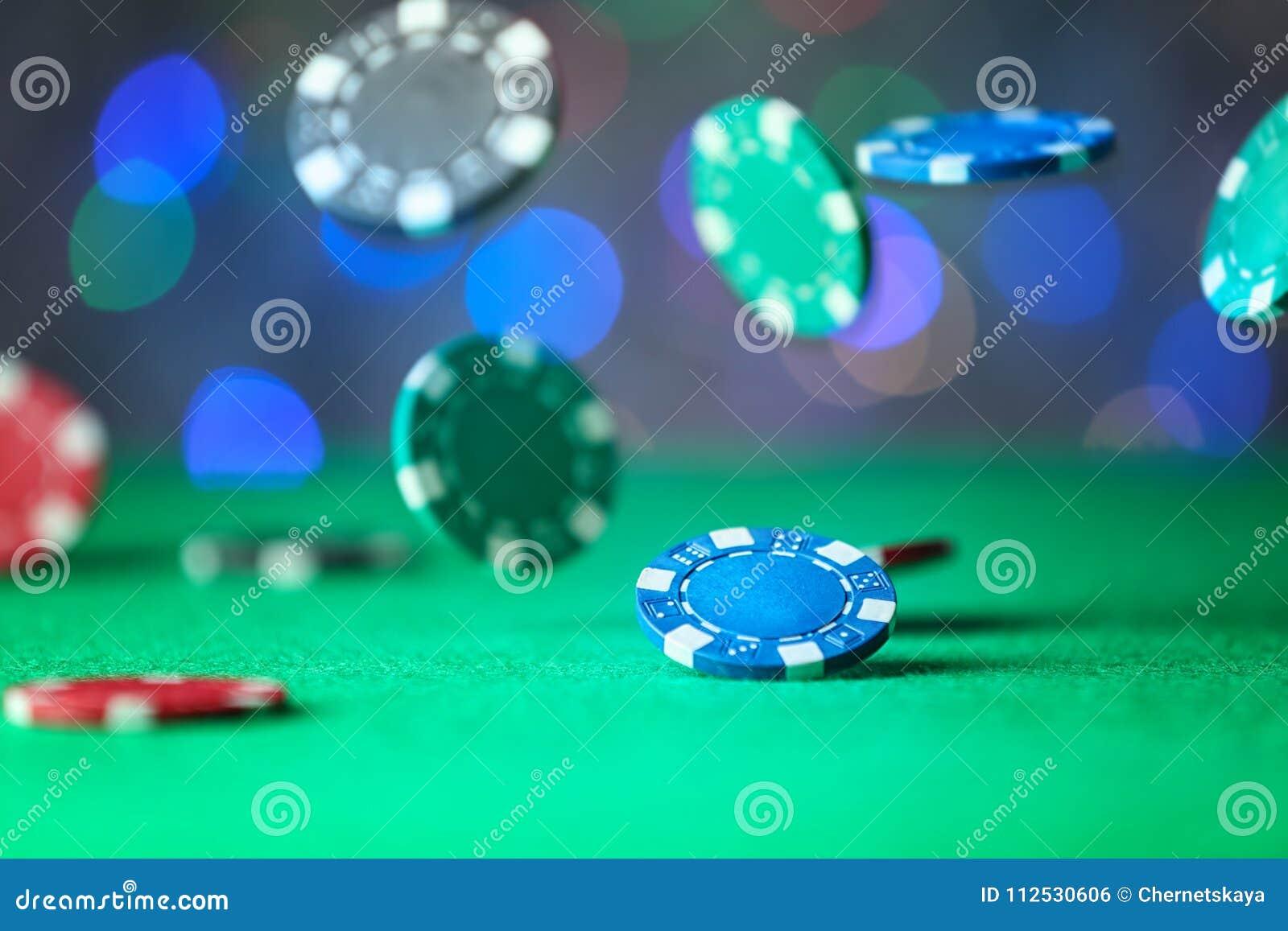 Gambling chips falling on green table