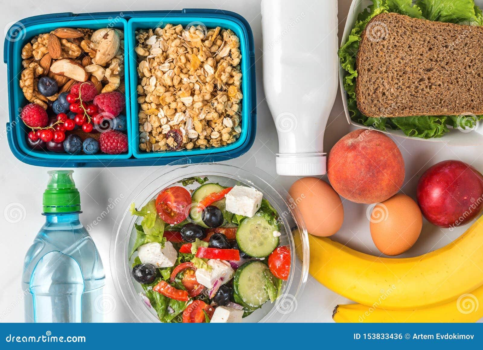 Gamelles avec la nourriture saine à emporter pour la journée entière granola de petit déjeuner avec du yaourt, salade grecque, sa