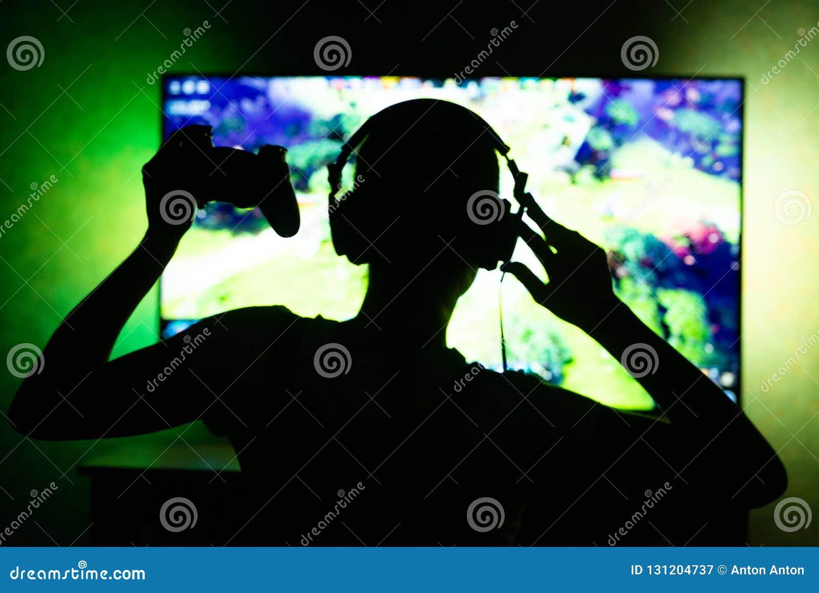 Gamer девушки в наушниках в предпосылке темноты по телевизору Способность использовать как предпосылка силуэт