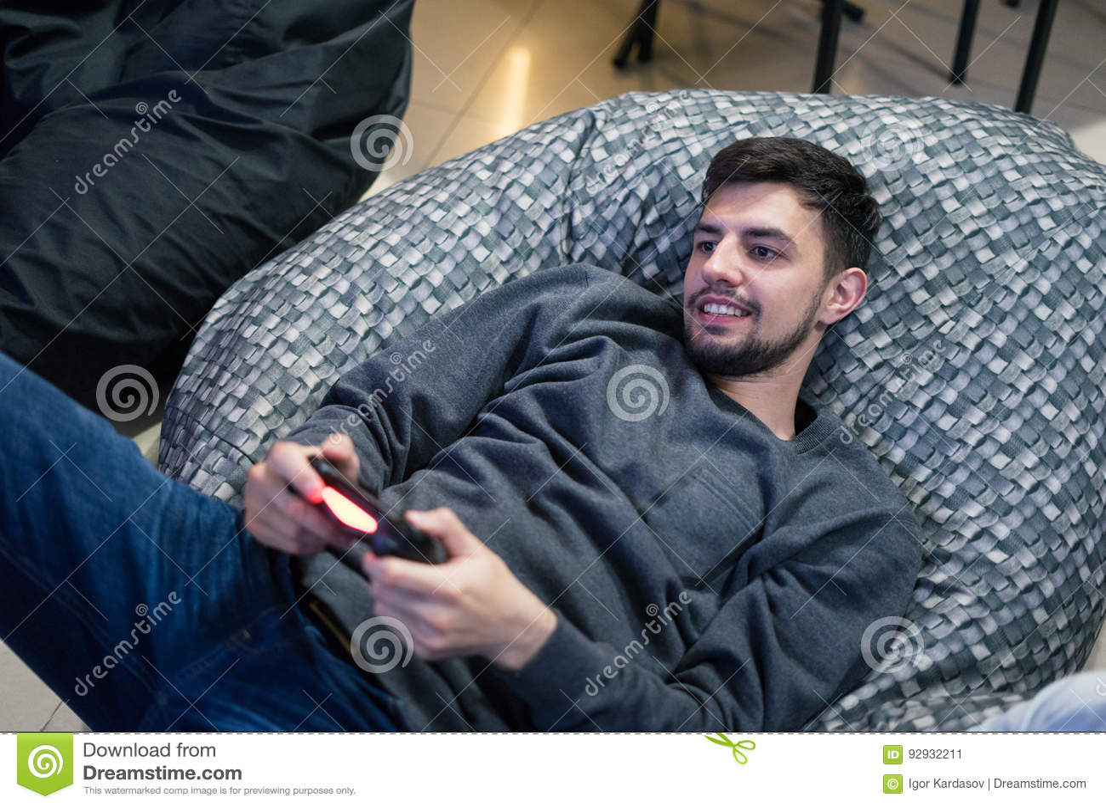 Gamer играя видеоигры при кнюппель сидя на стуле сумки фасоли