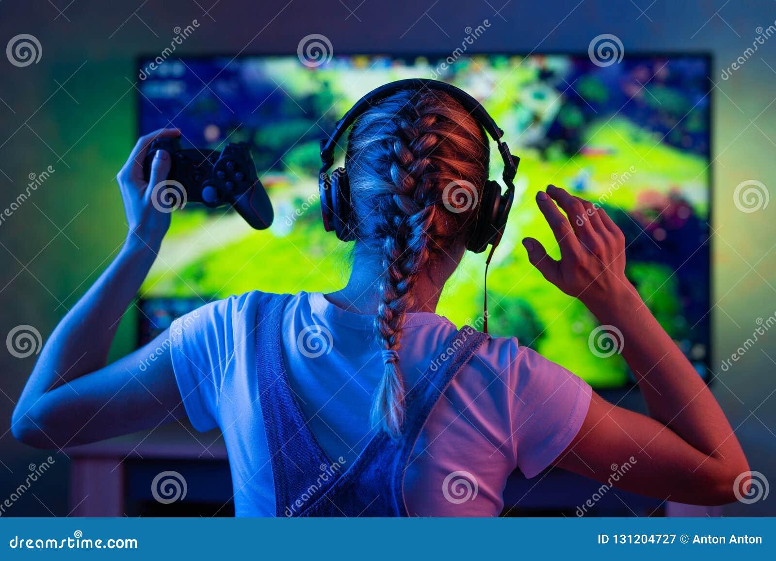 Gamer lub streamer dziewczyna w ciemnym pokoju z gamepad bawić się z przyjaciółmi na sieciach w gra wideo w domu Młody człowiek