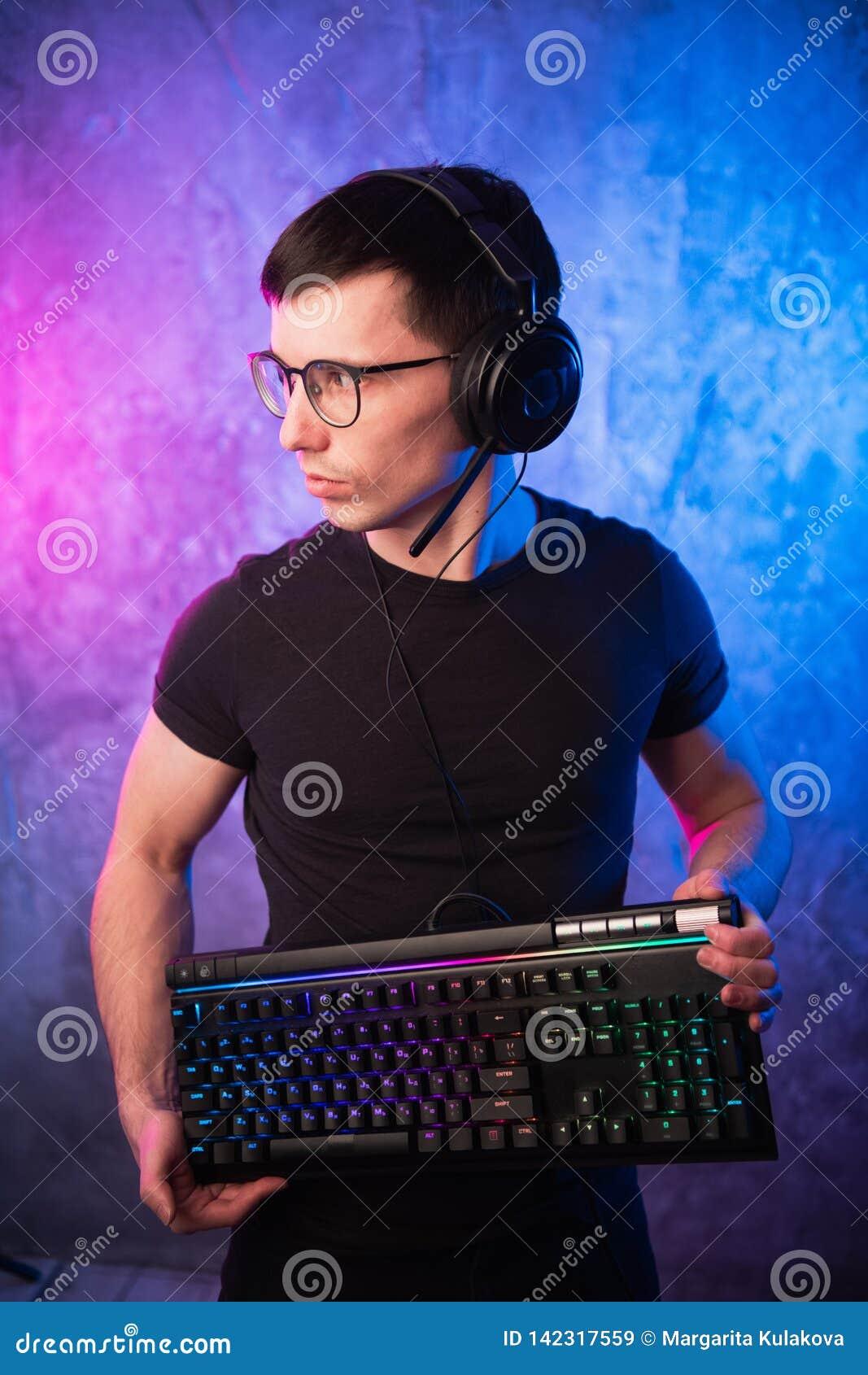 Gamer profissional do menino que guarda o teclado do jogo sobre o rosa colorido e a parede leve de néon azul Conceito dos gamers