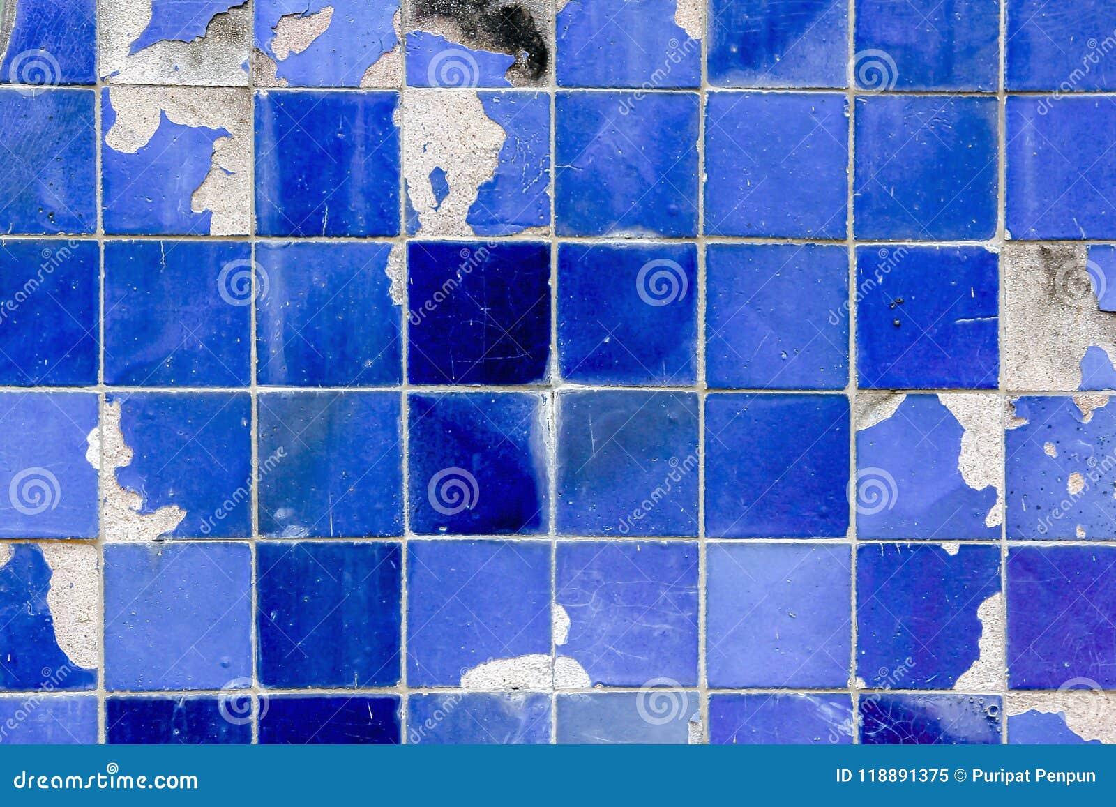 Gamla blått belägger med tegel väggen med sprickor och faller av