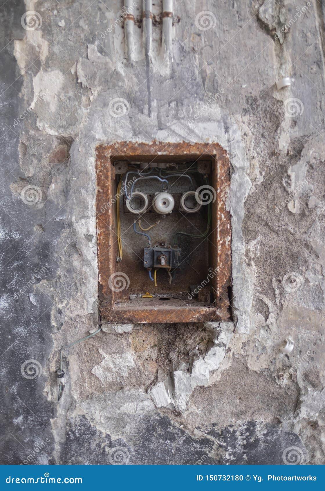Gamla dåliga Rusty Switch Box på den red ut väggen