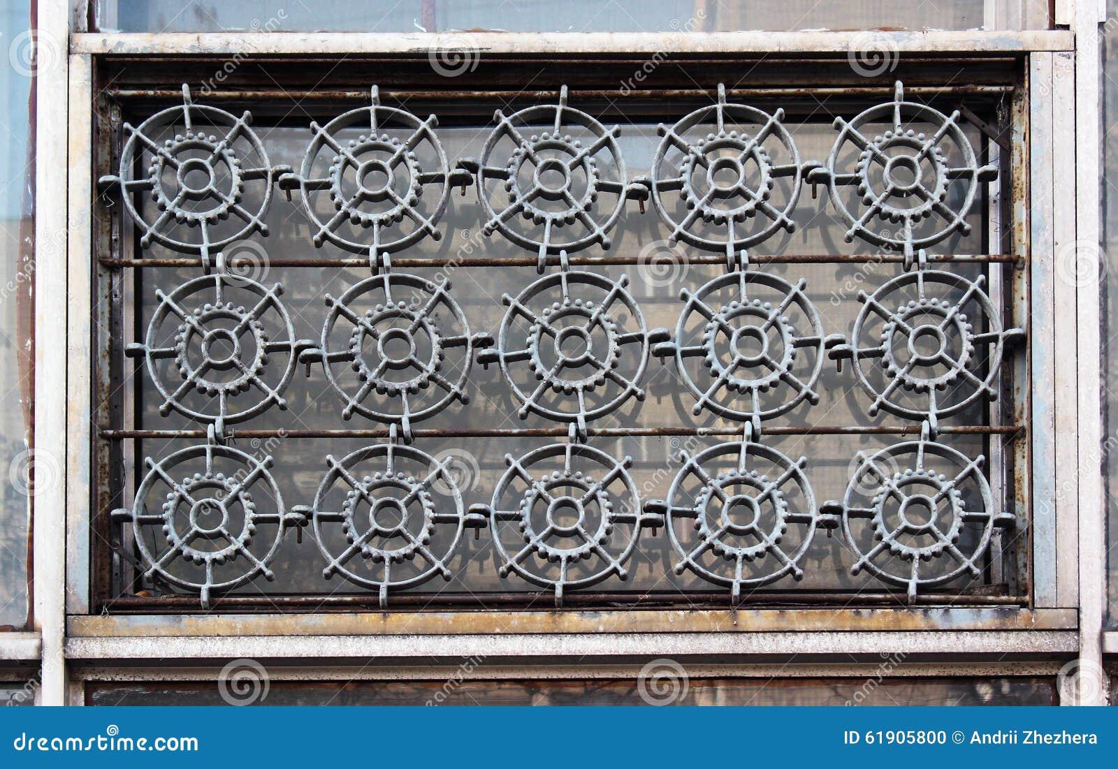 Gamla fönster med järnspisgallret formade som kugghjul