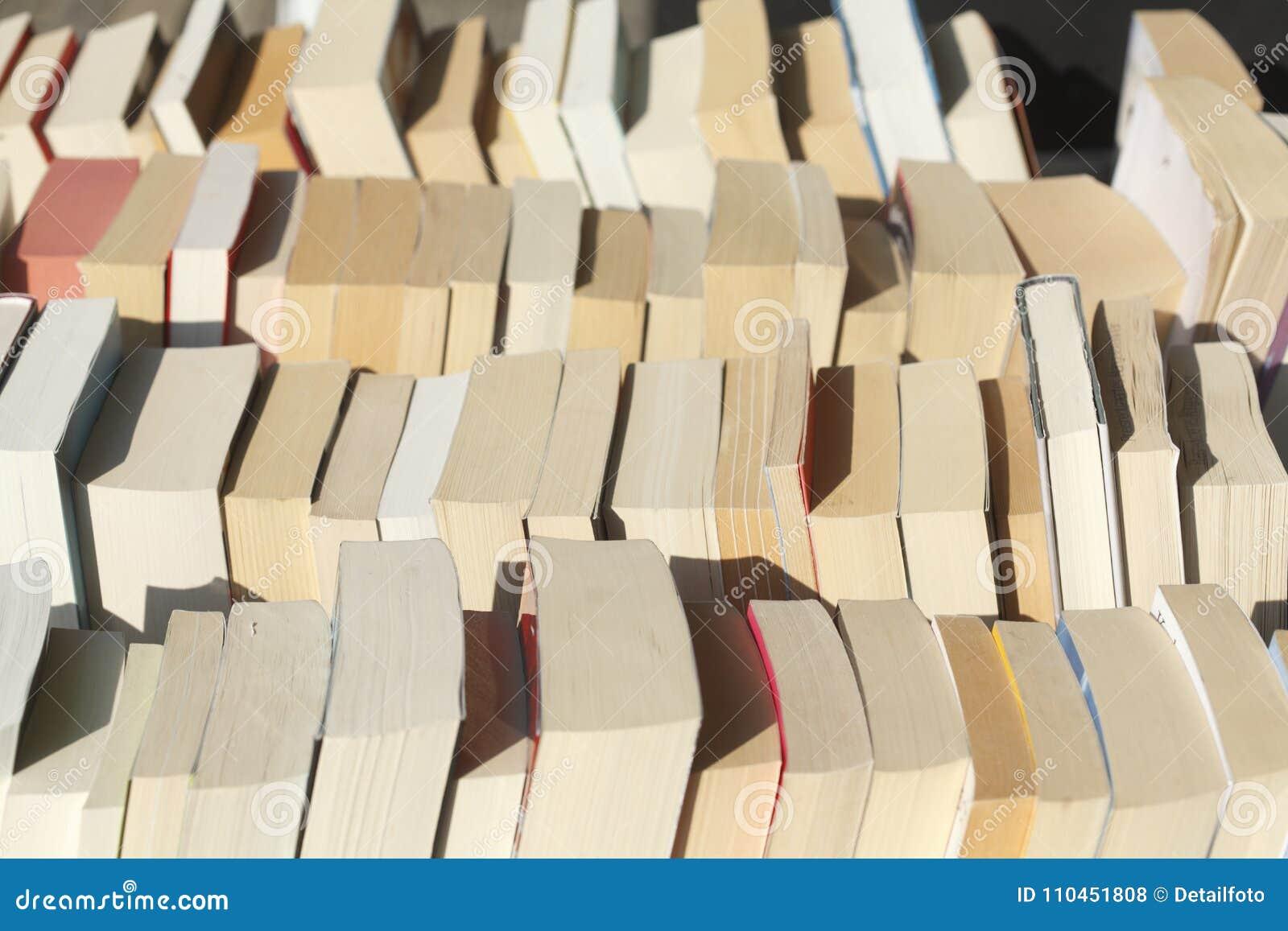 Gamla häftade böcker i en bokhylla