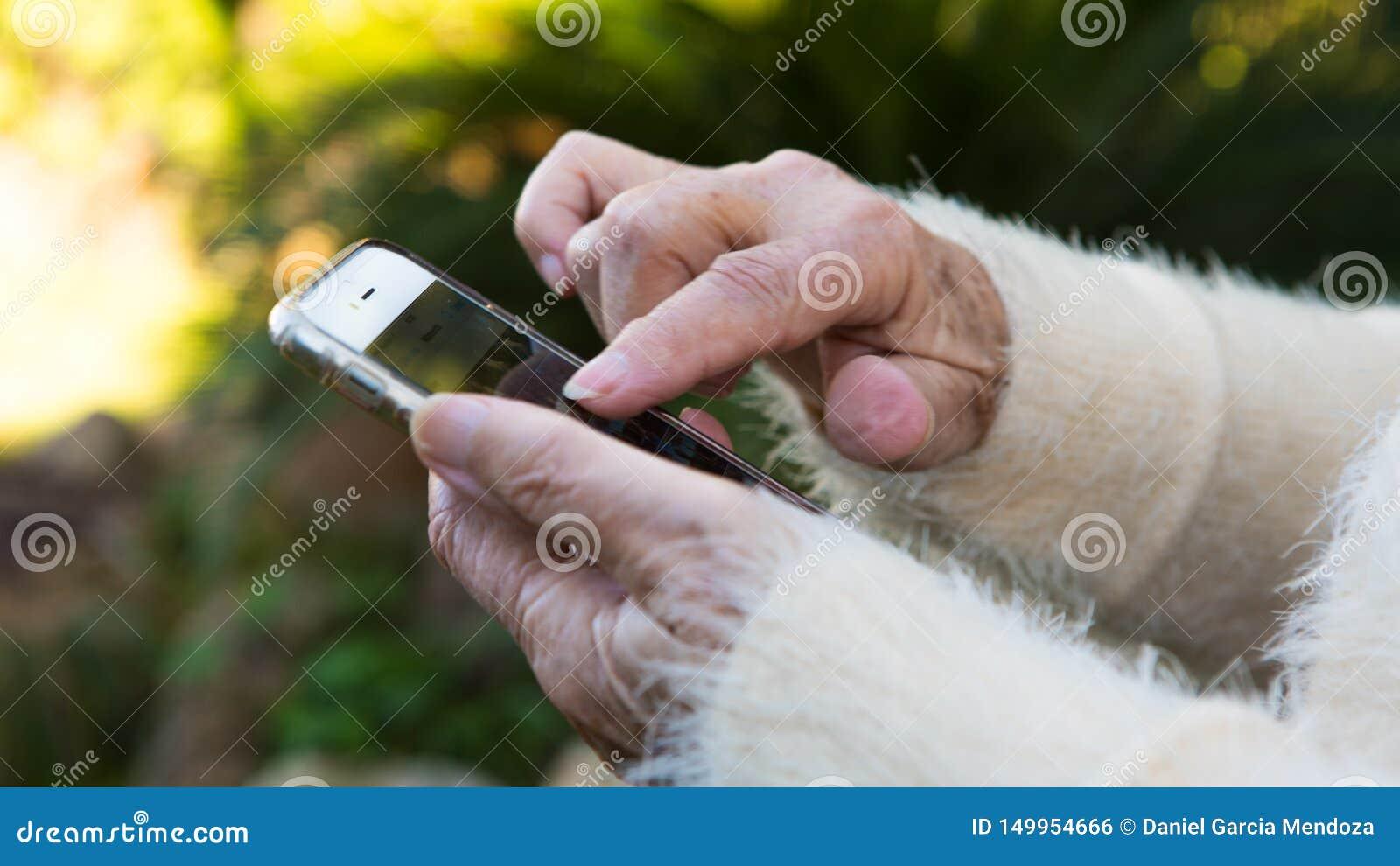Gamla händer av farmodern som rymmer en mobiltelefon i trädgårdhuset