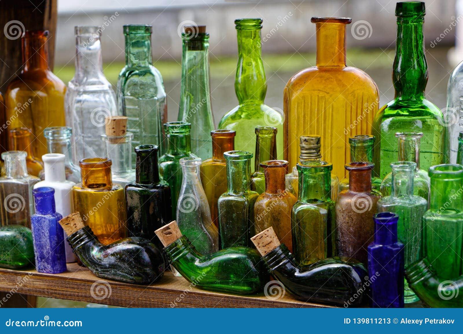Gamla kulöra tomma glasflaskor är knappa
