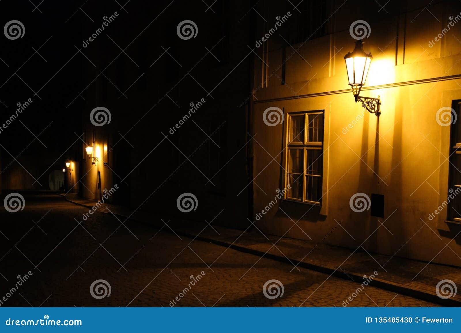 Gamla lyktor som exponerar en medeltida gata för mörk bakgata på natten i Prague, Tjeckien Lågt nyckel- foto med bruntgulingsigna