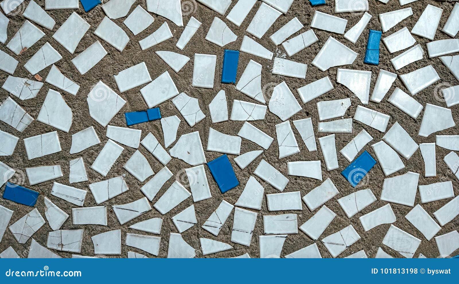 Gamla tegelplattor i betong, mosaik, bruten keramik i byggnaden Bakgrund av ett hus i staden