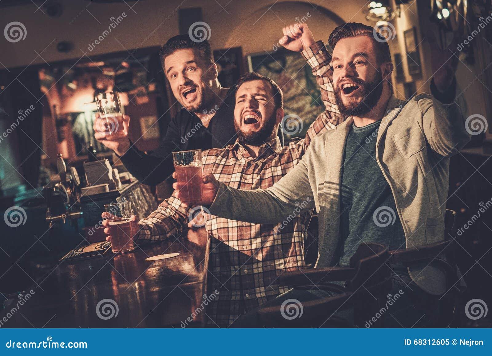 Gamla vänner som har gyckel som håller ögonen på en fotbolllek på TV och dricker utkastöl på stångräknaren i bar