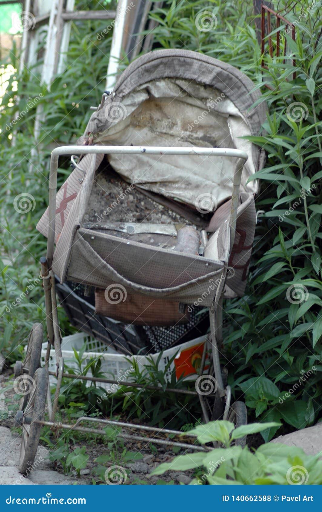 Gammal barnvagn i trädgården
