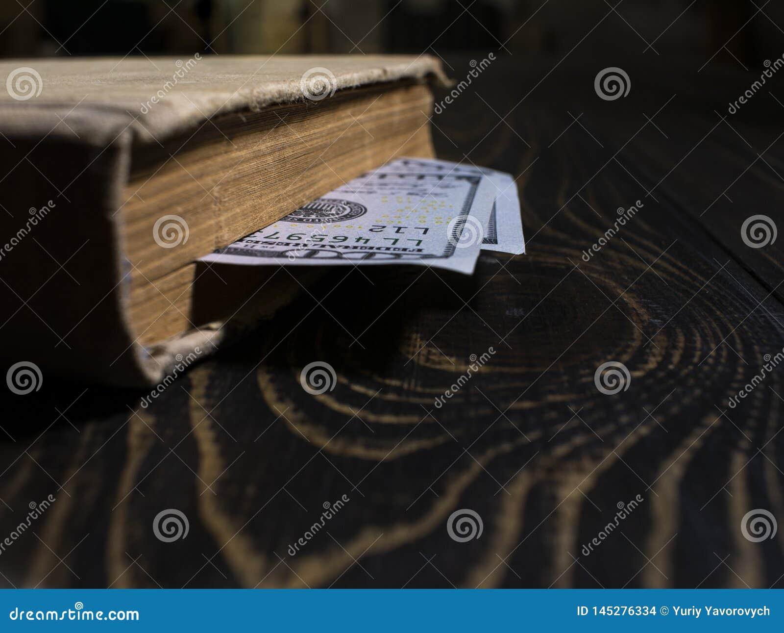 Gammal bok och tvåhundra dollar bokmärke i en tjock bok bok på bakgrunden av en trätabell
