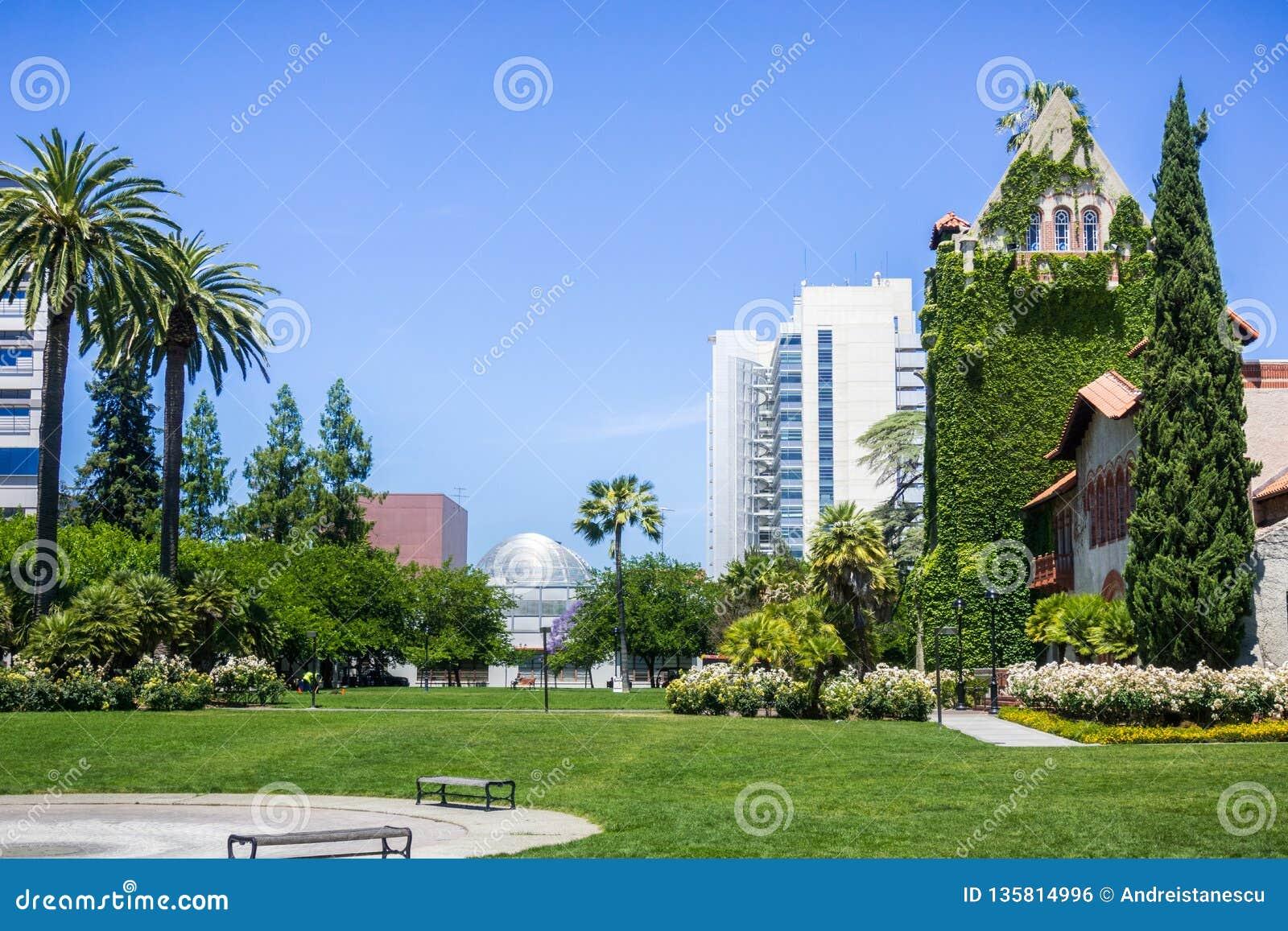 Gammal byggnad på Sanen Jose State University; den moderna stadshusbyggnaden i bakgrunden; San Jose Kalifornien