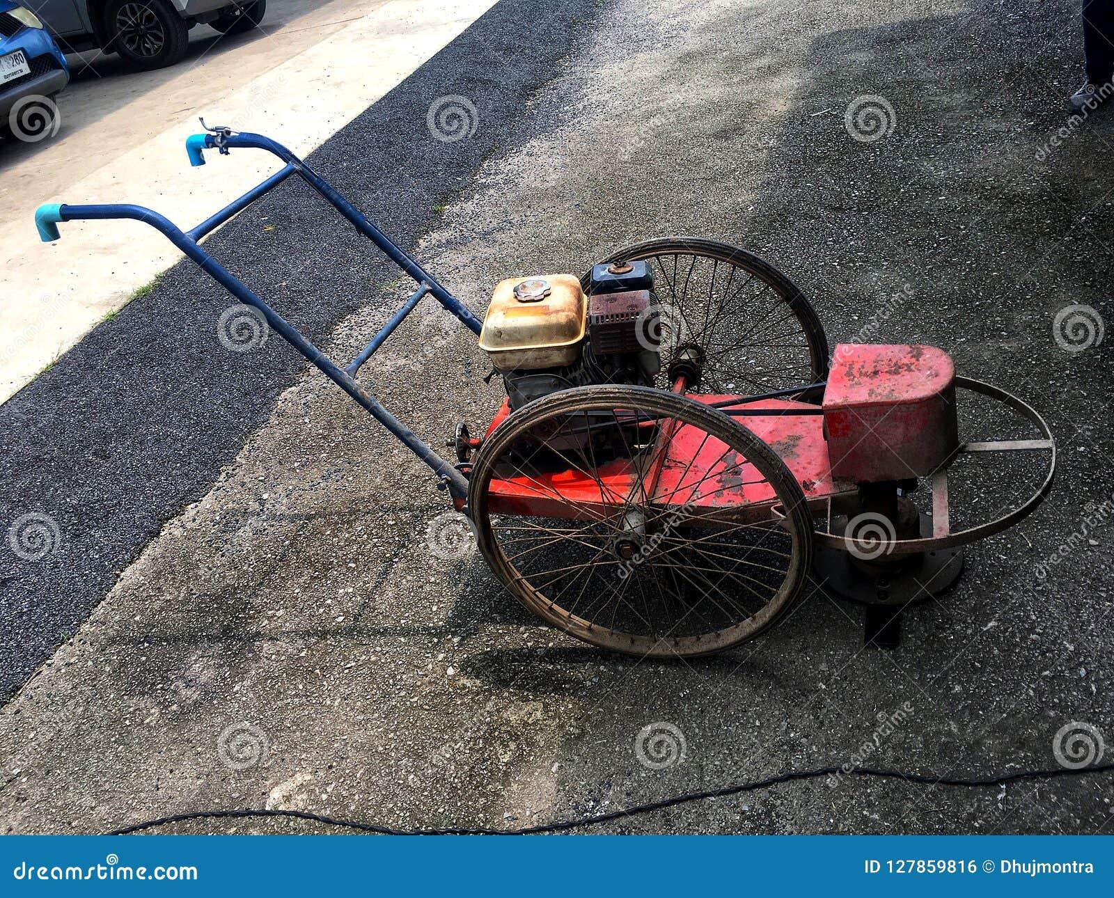 Gammal diesel- gräsklippare på kiselstengolvet