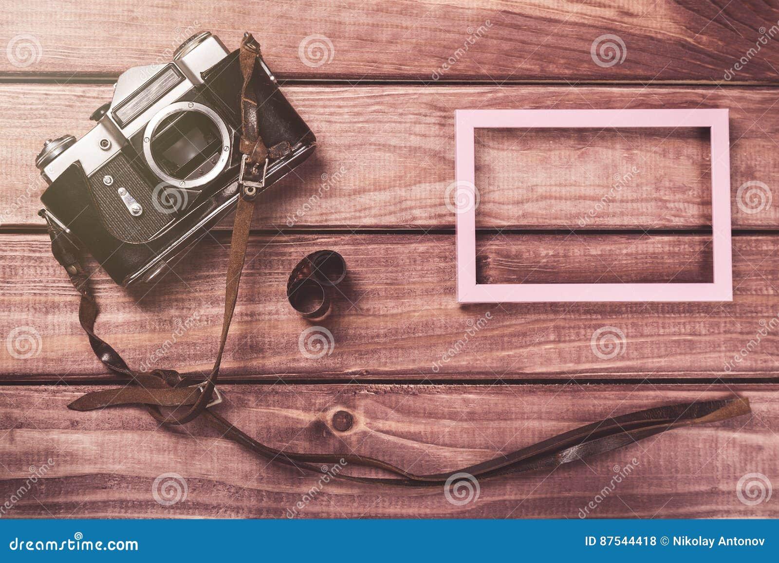 Gammal filmkamera med remmen, fotoramen och filmen på träbakgrund Tonad och bästa sikt för tappning