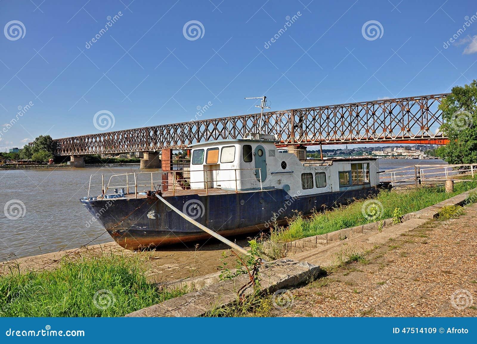Gammal fiskebåt och bro bakom