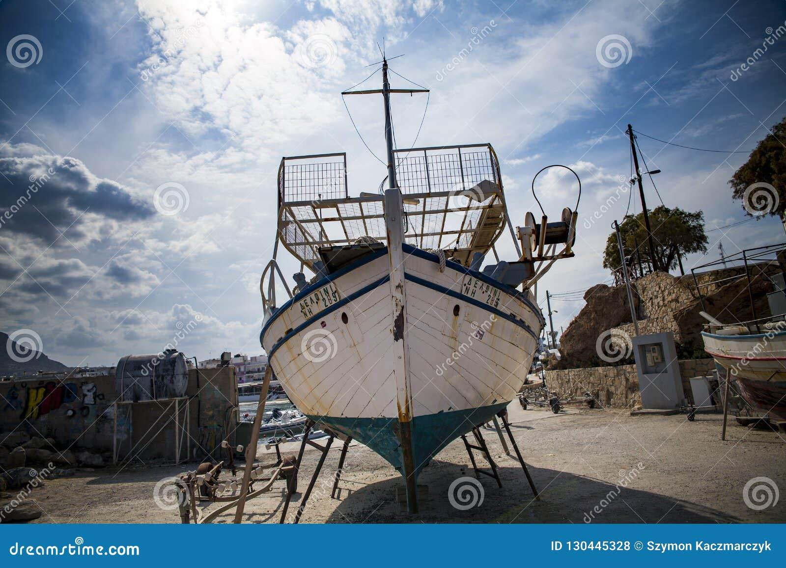 Gammal fiskebåt på kusten Ett skepp drog ashore Hamn i byn av Hersonissos på ön av Kreta, Grekland