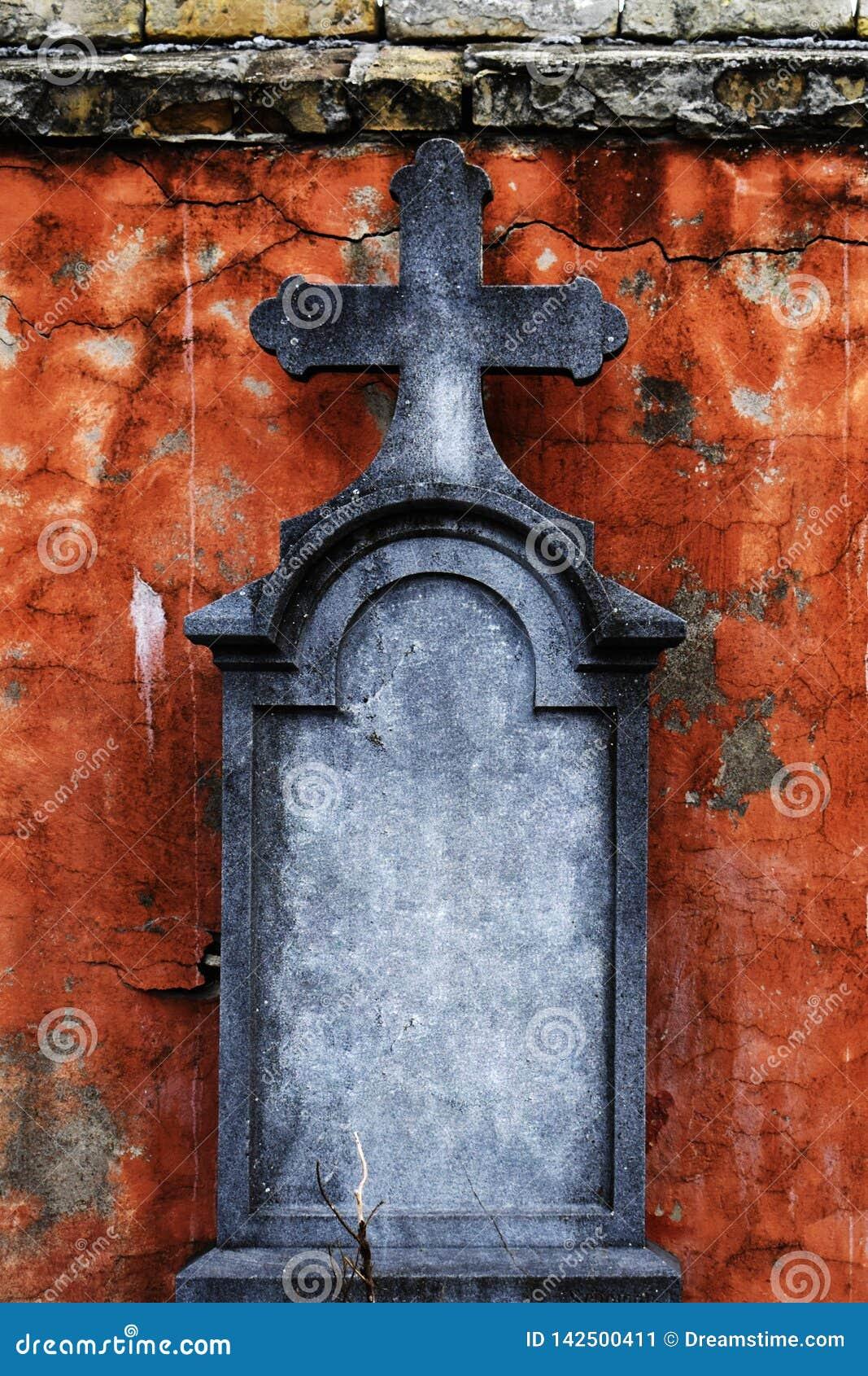 Gammal gravsten med korset framme av att smula fasaden