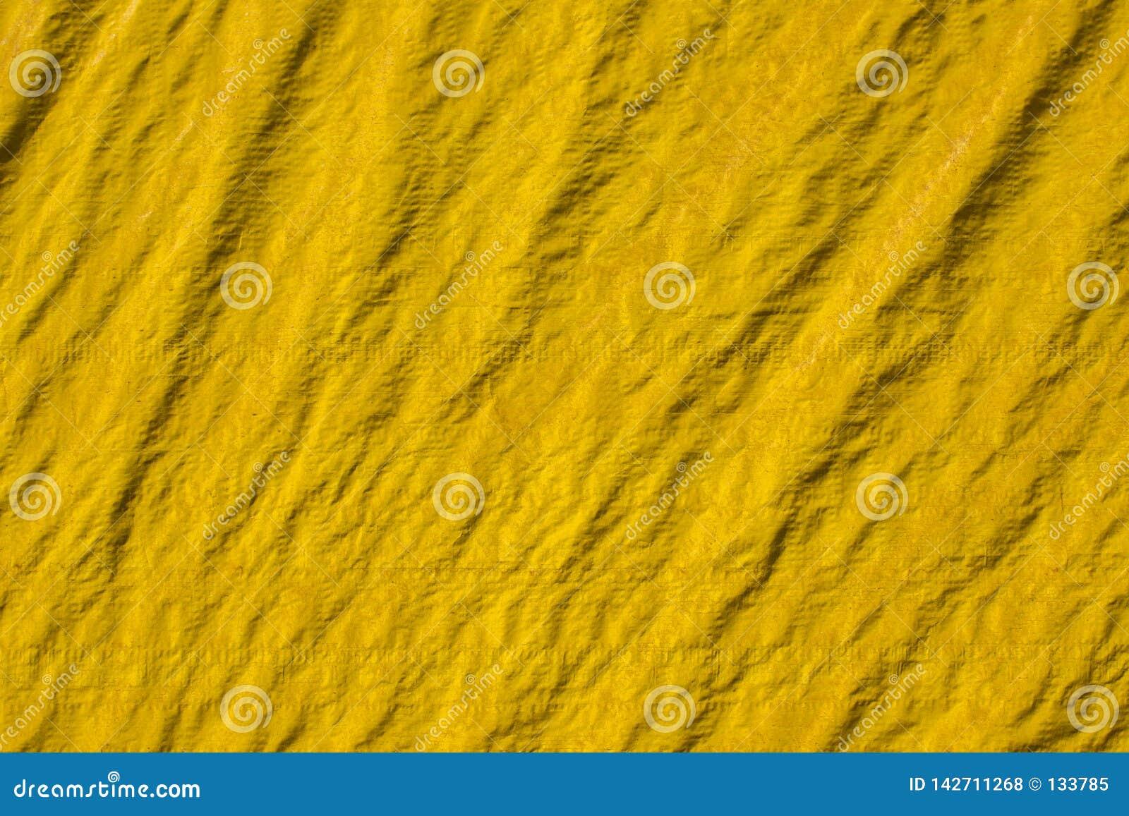 Gammal gul skrynklig kanfas med veck och skuggor Textur för grov yttersida