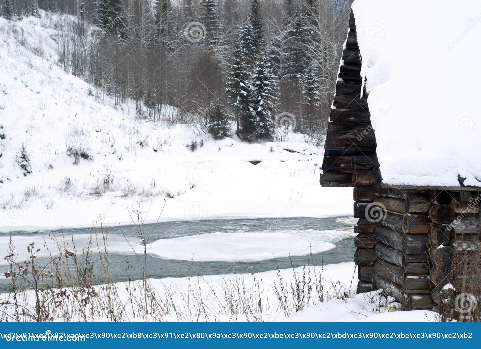 Gammal journalkoja på flodbanken i vinterlandskapet