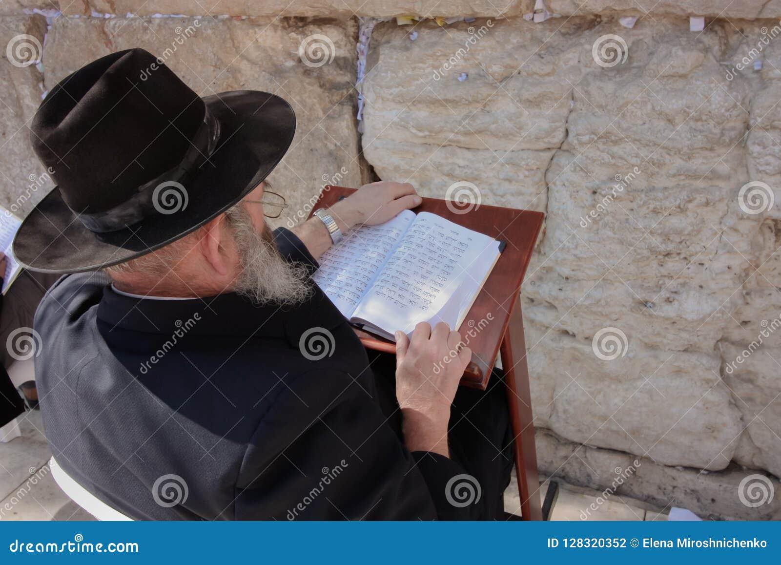 Gammal judisk man läsande Tora på den att jämra sig väggen