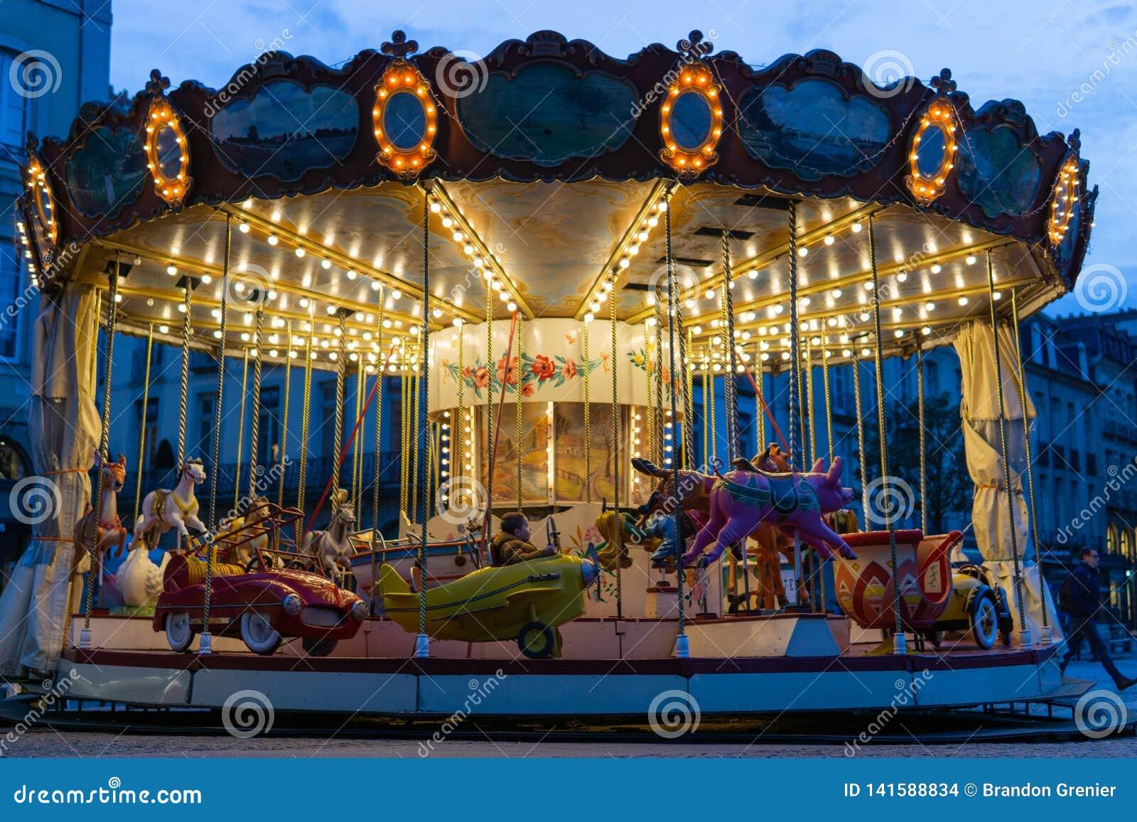 Gammal karusell för ung pojkeridning på natten med ljusa ljus