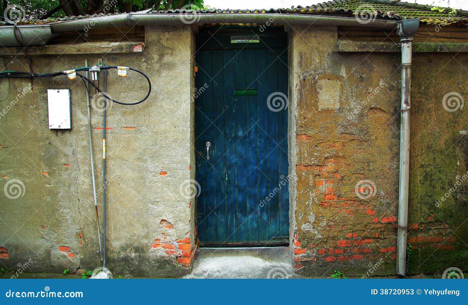 Gammal kinesisk husvägg med den blåa dörren