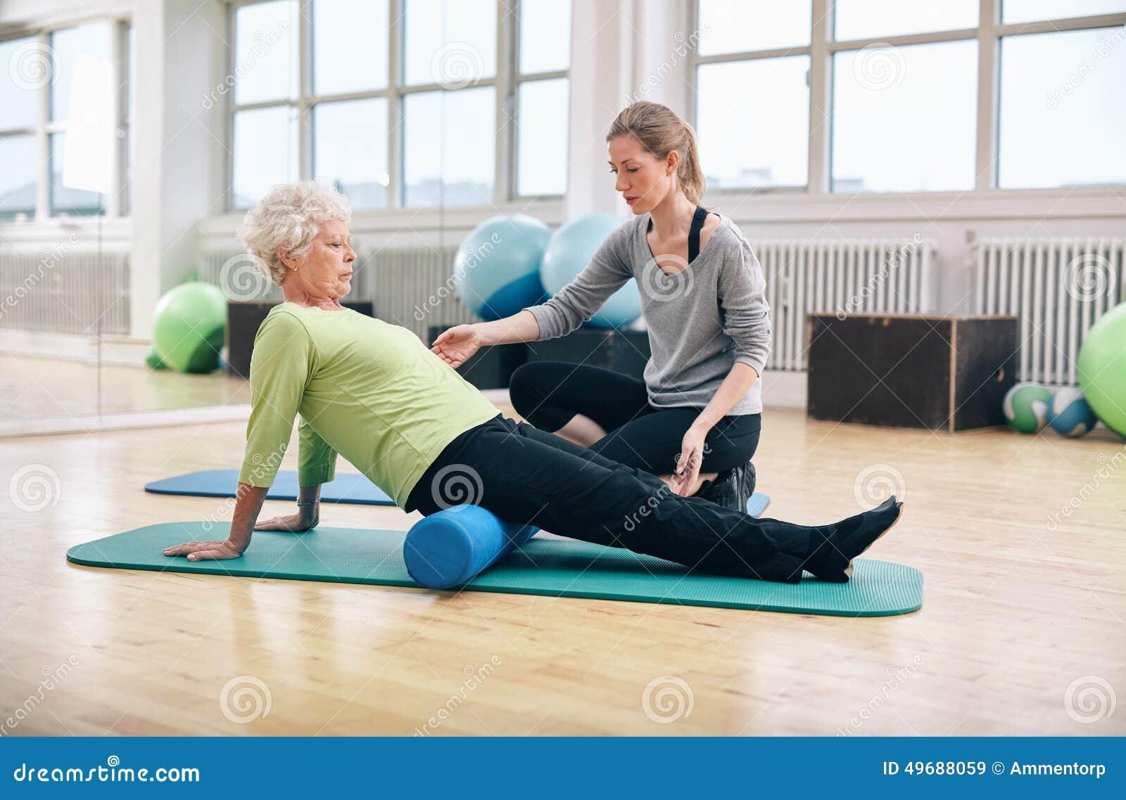 Gammal kvinna som använder skumrullen med den personliga instruktören