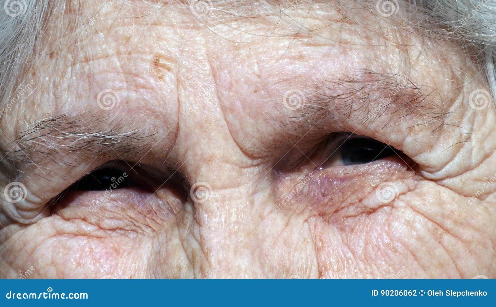 Gammal kvinna som ser kameran och att le closeup