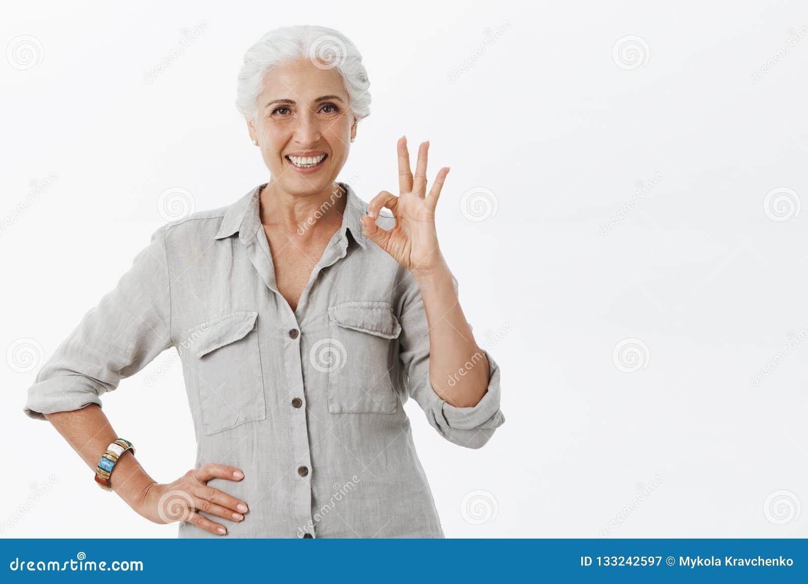 Gammal lycklig dam som försäkrar hennes pengar i säkert ställe tack vare banken Stående av nöjd säker och förtjust gullig åldring
