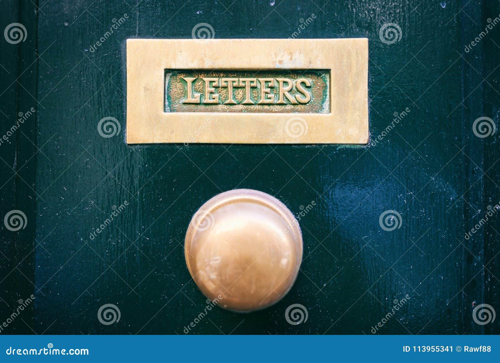 Gammal mässingspostbrevlåda och knopp på en gräsplan målad ytterdörr, textbokstäver