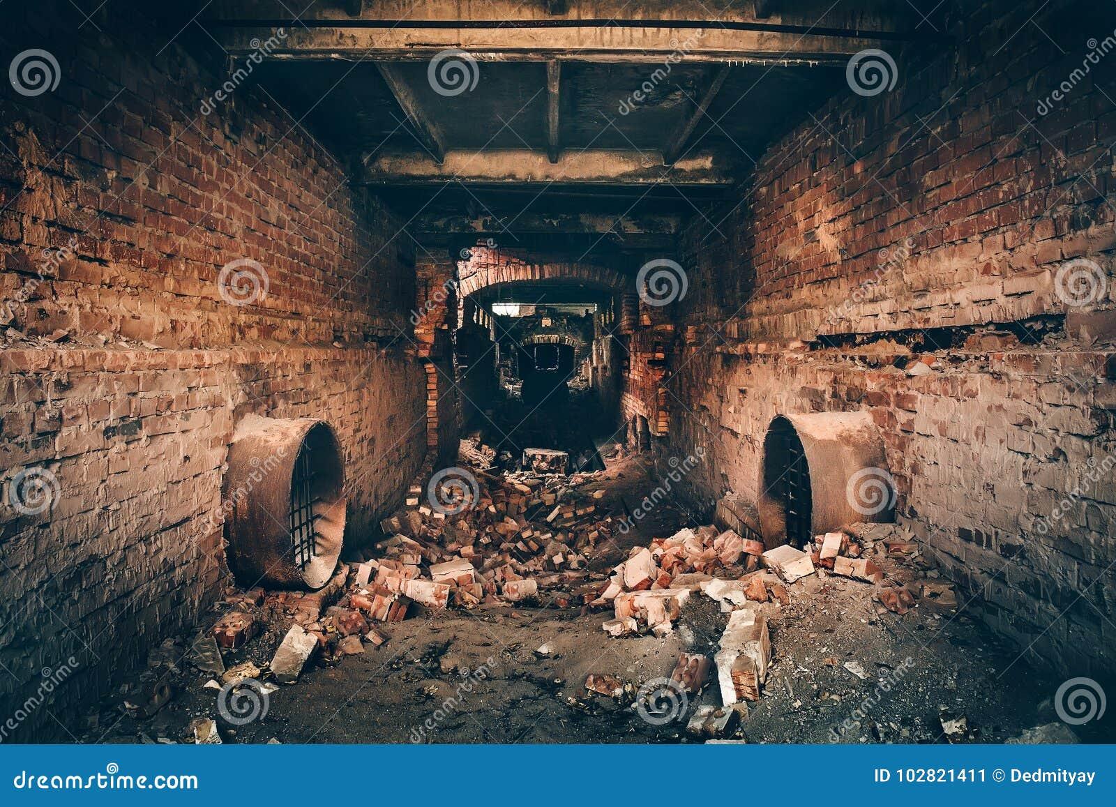 Gammal mörk kuslig underjordisk tegelstentunnel eller korridor eller avklopprörledning på den övergav förstörda industriella fabr