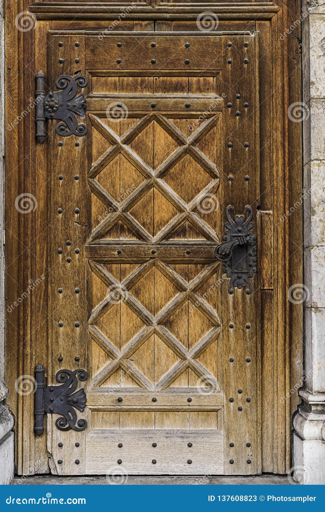 Gammal massiv dörr med ett stort metallhandtag