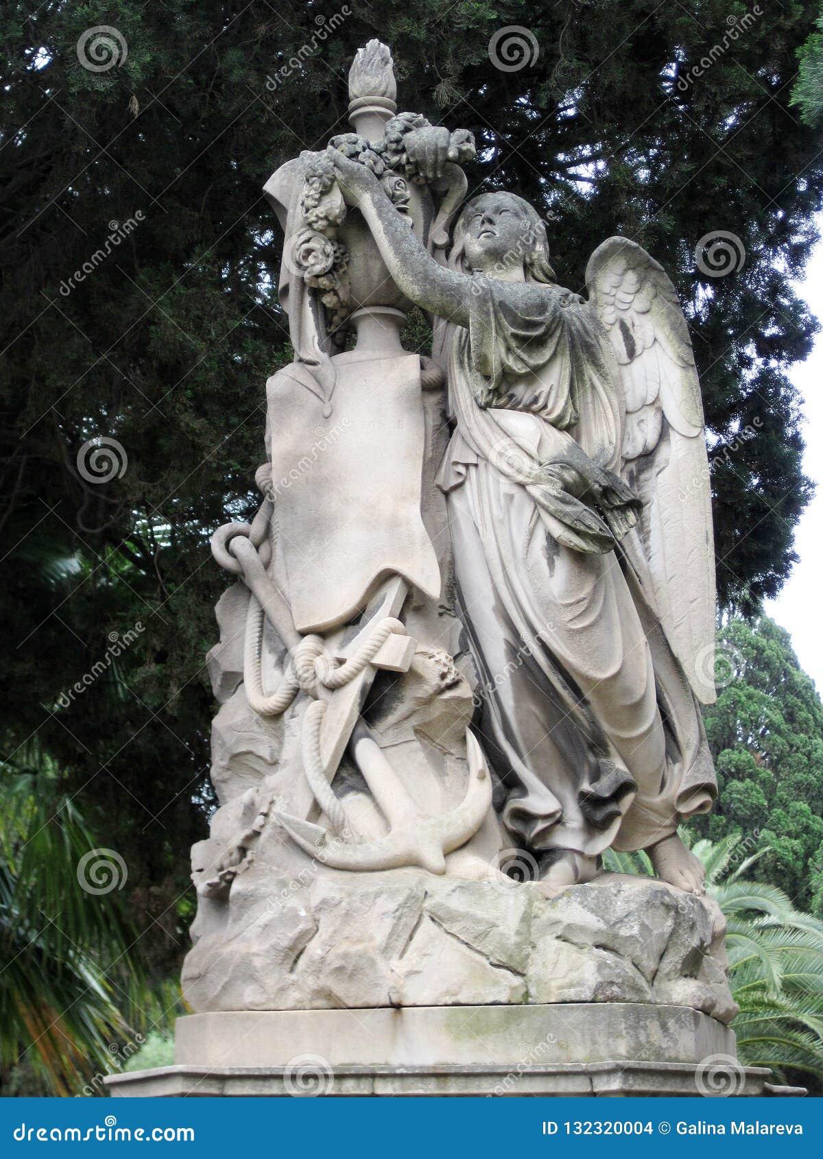 Gammal monument som grubblar ängel på en sockel med blommor och ett havsankare
