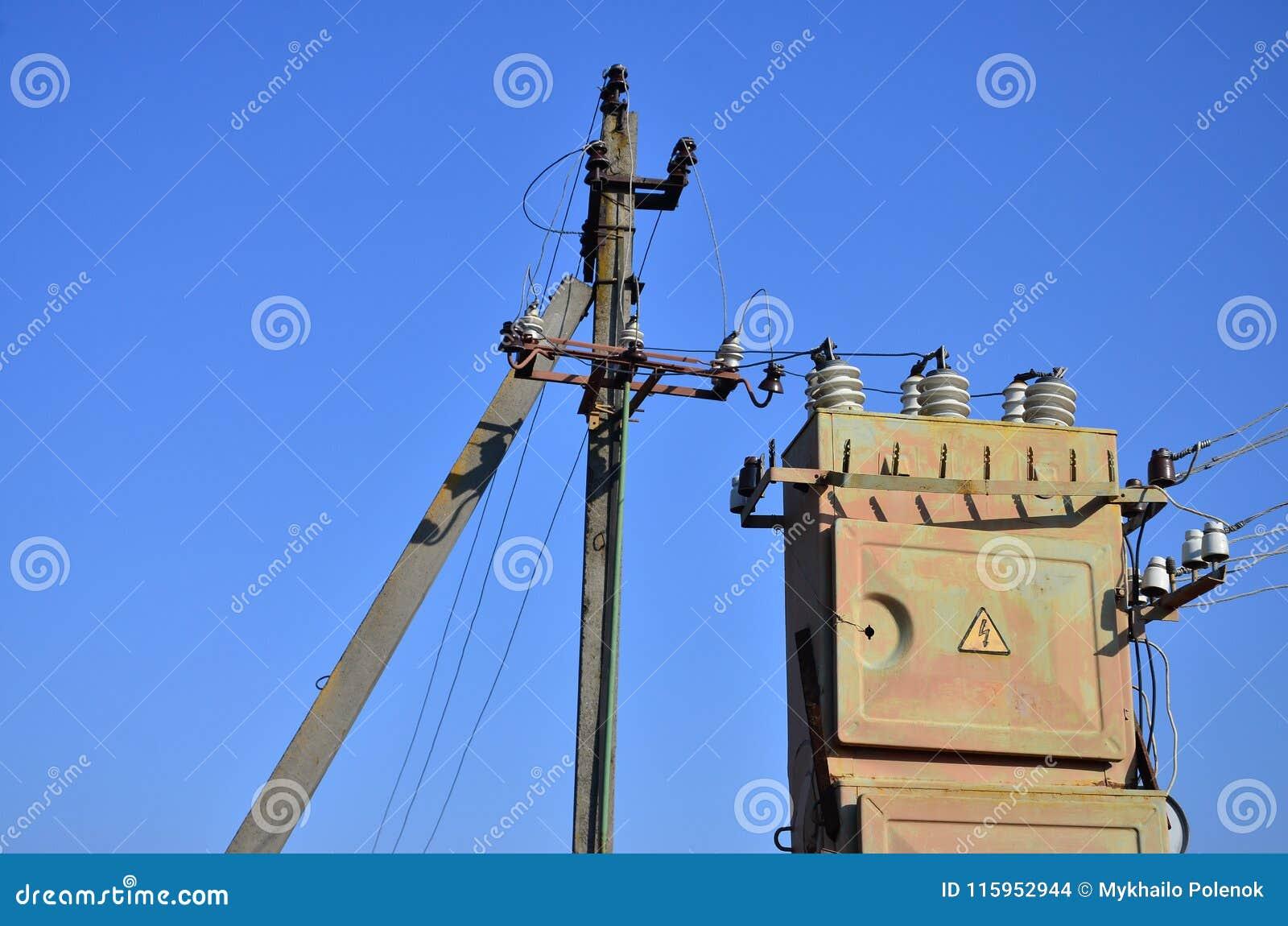 Gammal och föråldrad elektrisk transformator mot bakgrunden av en molnfri blå himmel Apparat för fördelning av tillförsel av höjd