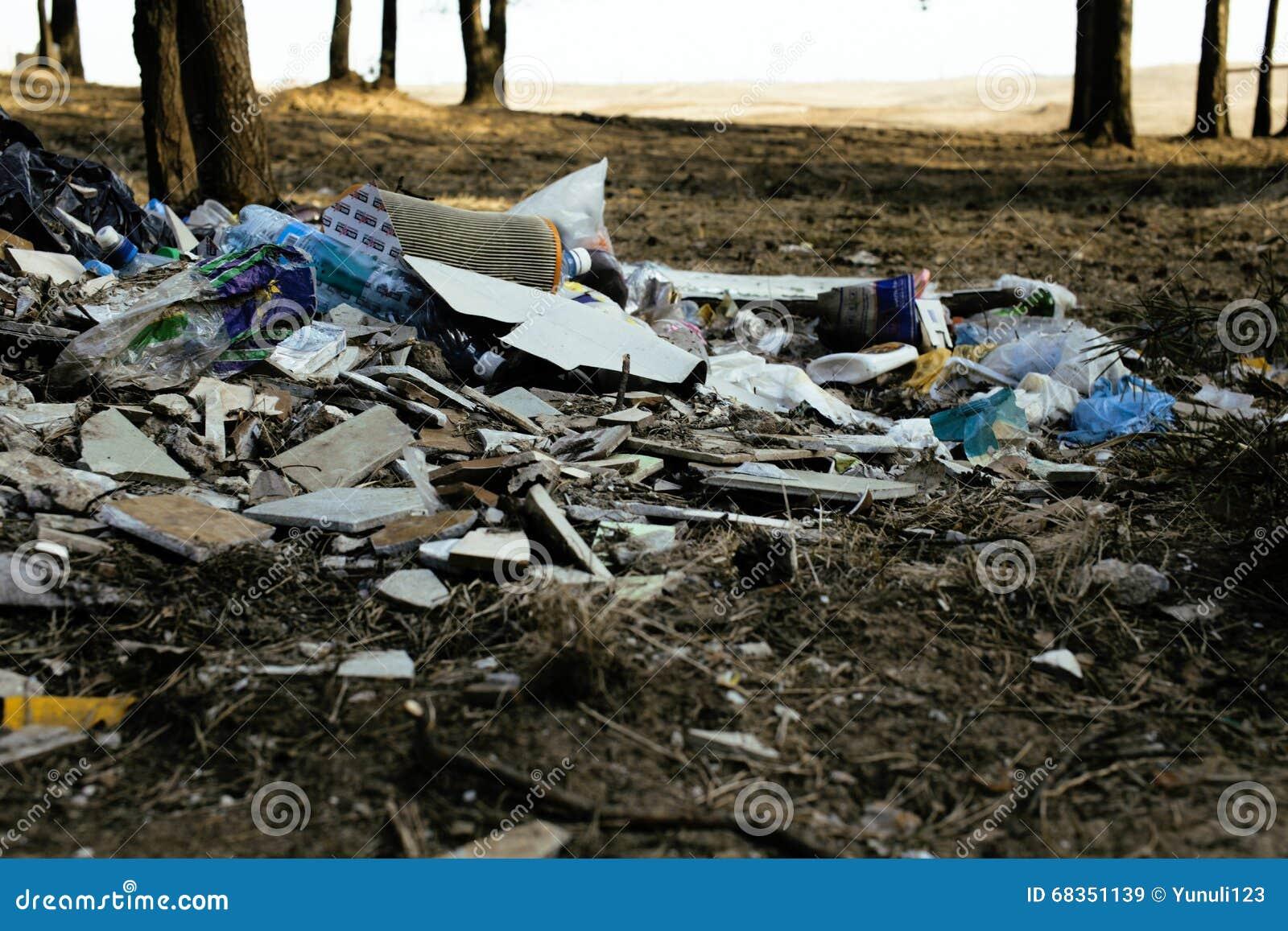 Gammal plast- avskräde i skogen, stort berg med inget omsorg av naturen, modernt miljöavfallbegrepp