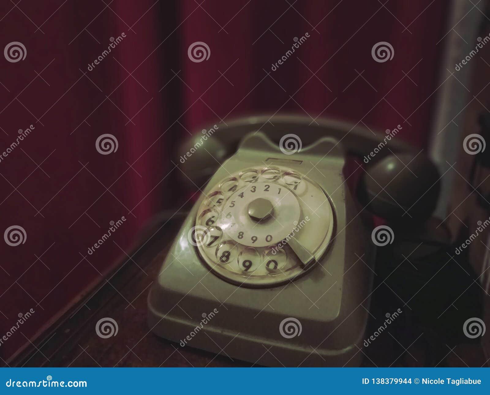 Gammal retro telefon på en trätabell med den röda gardinen på bakgrunden - gammalt foto, tappningstileffekt