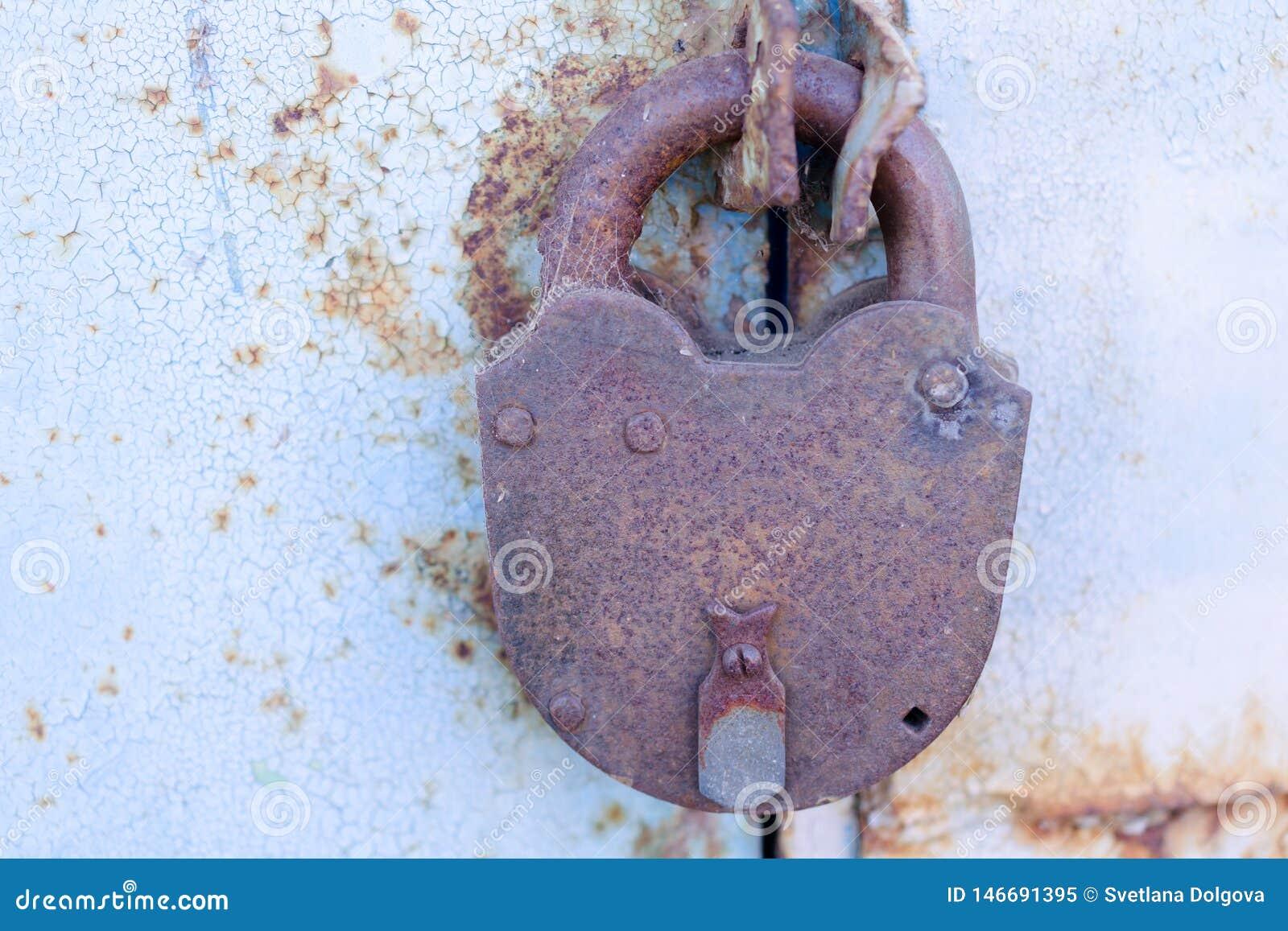 Gammal rostad hänglås på en metalldörr med sprucken blå målarfärg