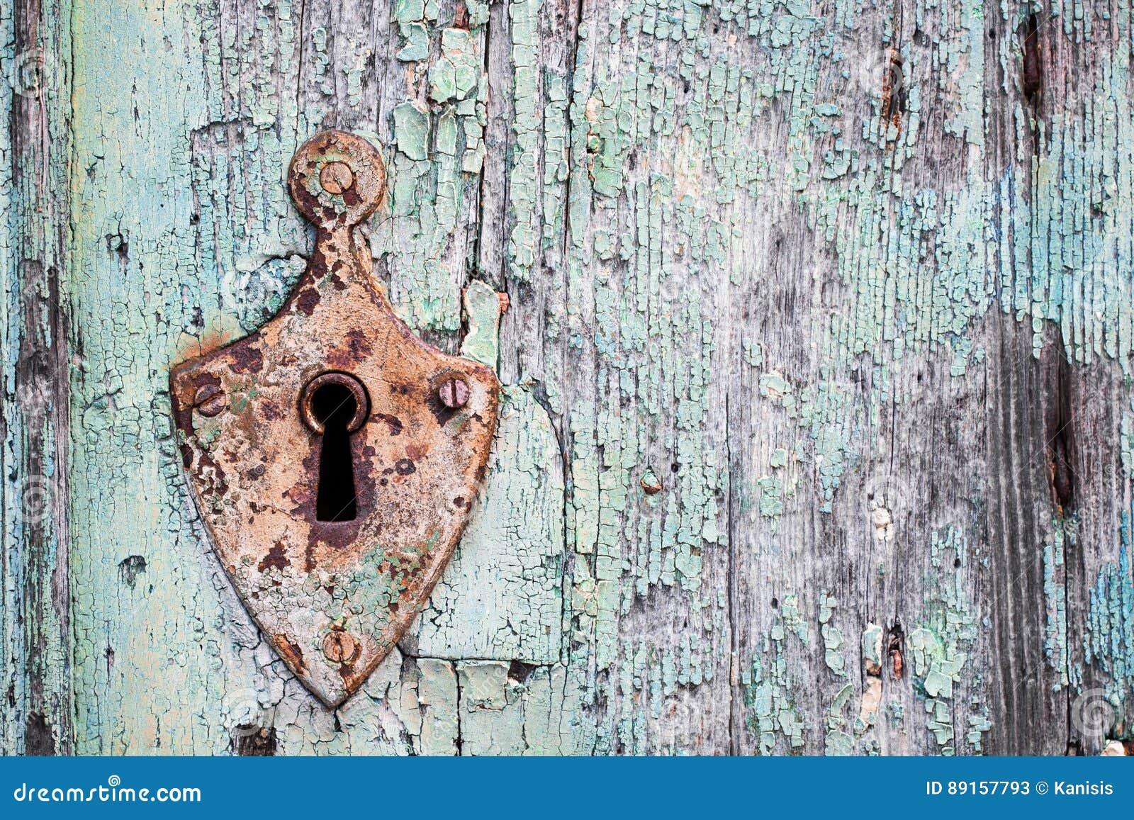 Gammal rostig metalllås och nyckelhål på en trädörr för gammal turkos