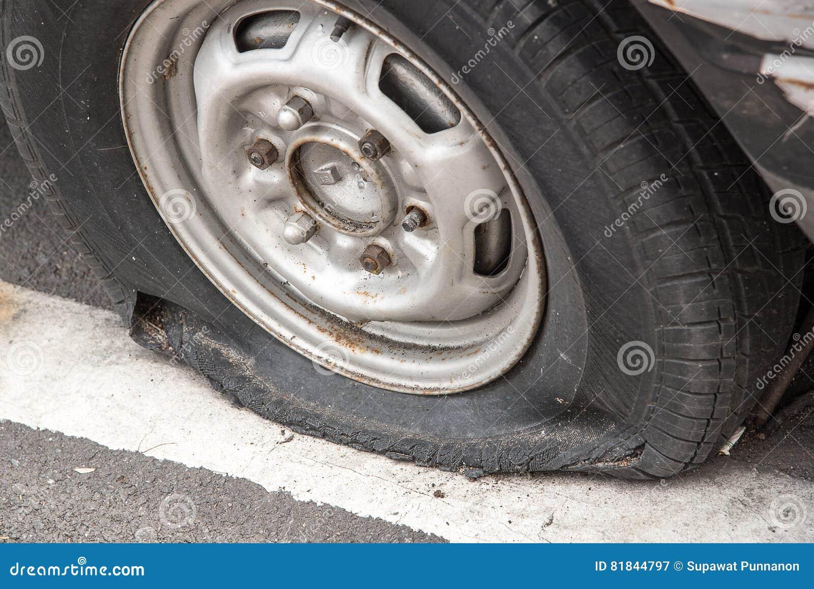 Gammal rostig skeppsbruten bil med ett punkterat gummihjul