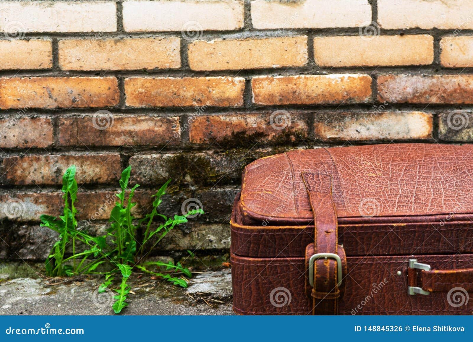 Gammal sjaskig resväska mot bakgrunden av en smutsig tegelstenvägg
