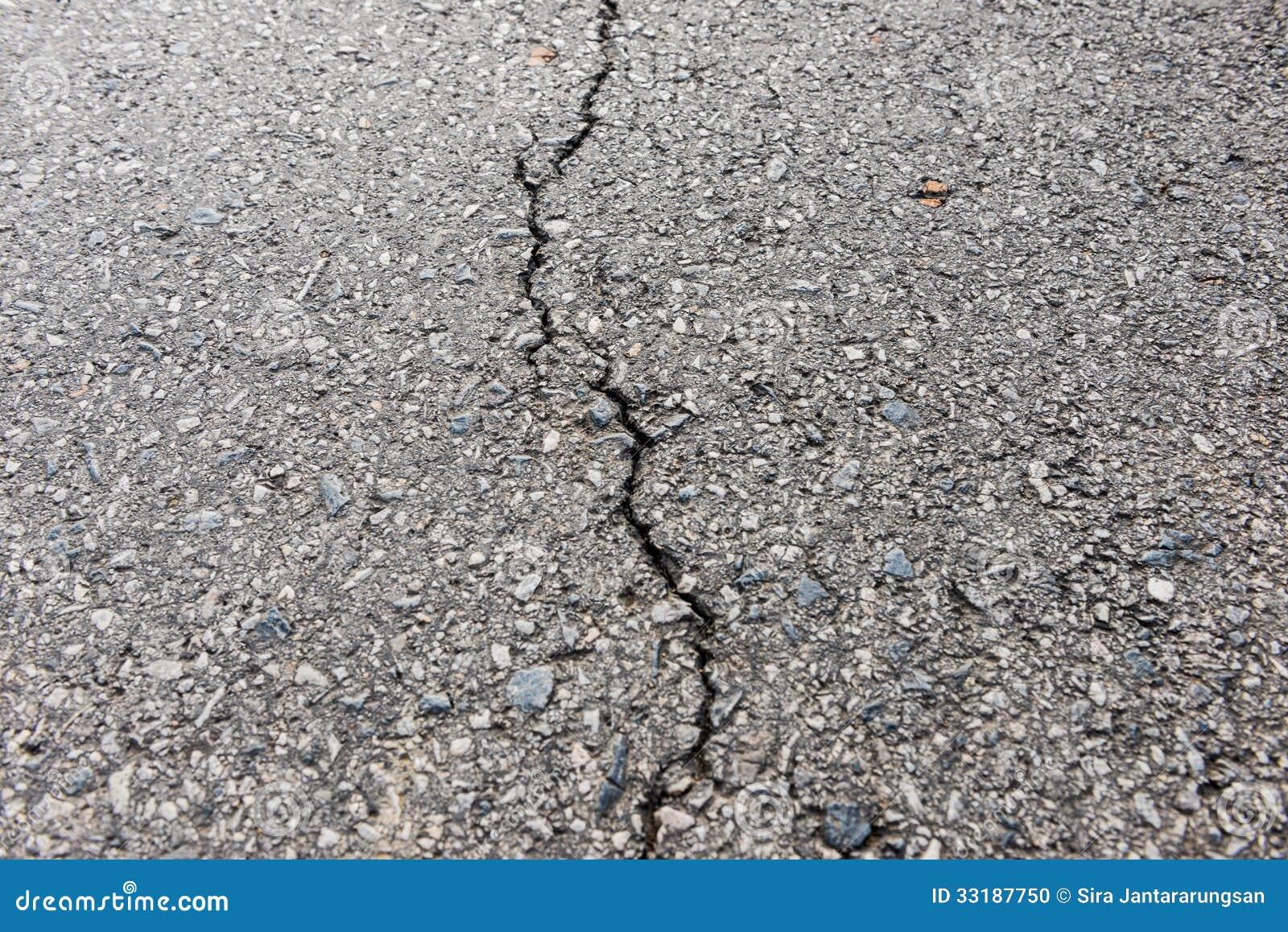 Gammal sliten och sprucken asfalt med sprickor