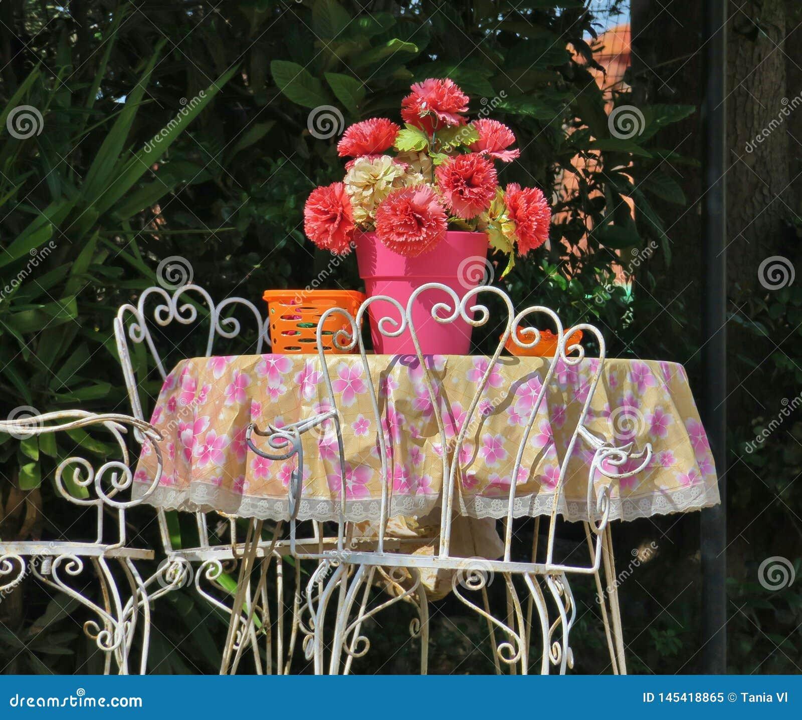 Gammal tabell i mitt av borggården med rosa blommor