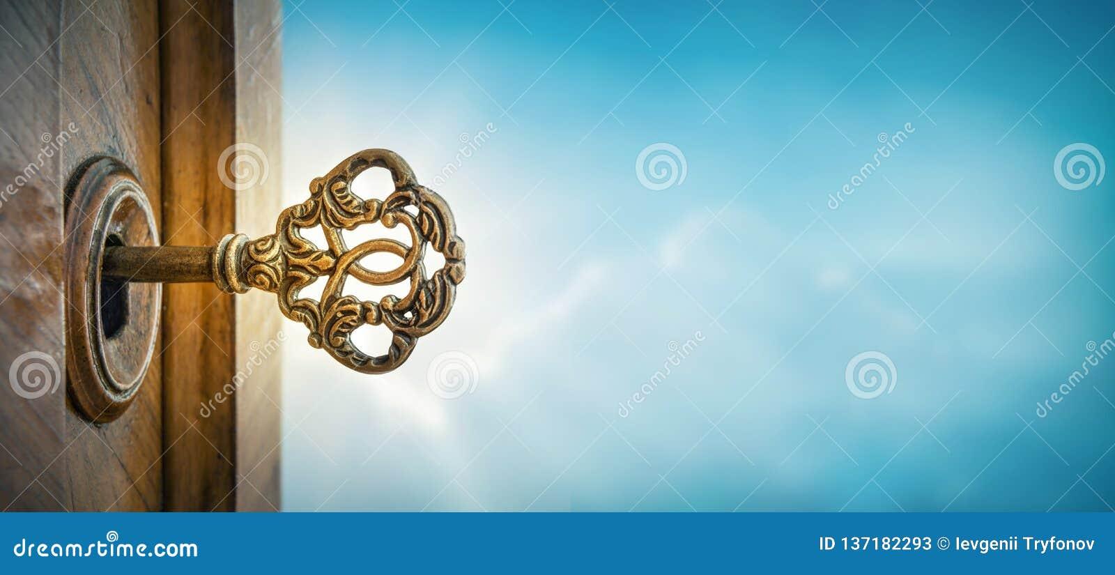Gammal tangent i nyckelhål på himmelbakgrund med solstrålen Begrepp, symbol och idé för historia, affär, säkerhetsbakgrund