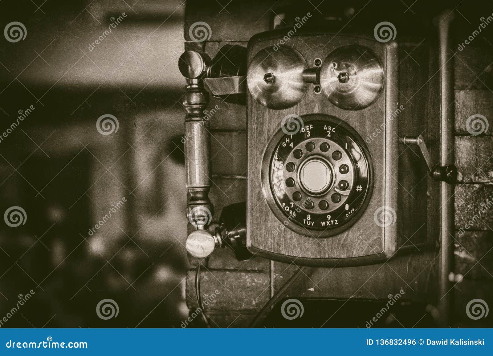 Gammal telefon för tappningväggmontering med mässingsklockor i monokromt - retro fotografi