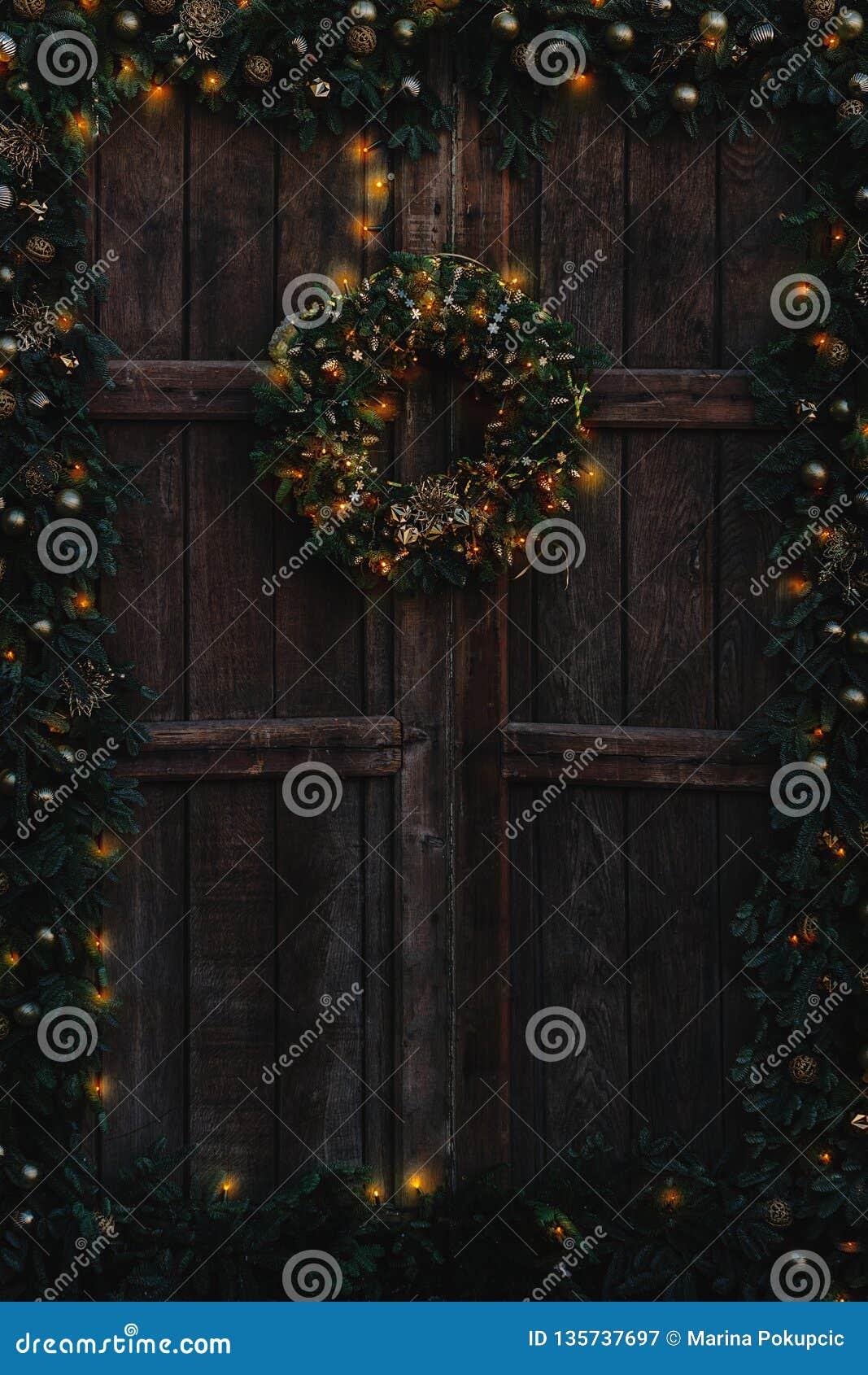 Gammal trädörr som dekoreras med jul girland och krans och med varma ljus