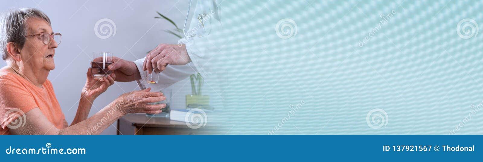 Gammalare kvinna som tar läkarbehandlingen panorama- baner