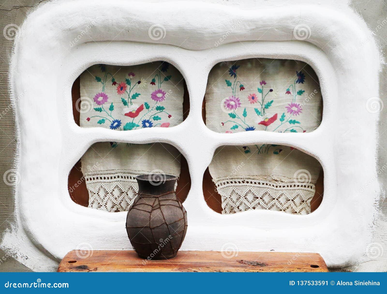 Gammalt fönster i den ukrainska byn Broderi och glechik på fönstret