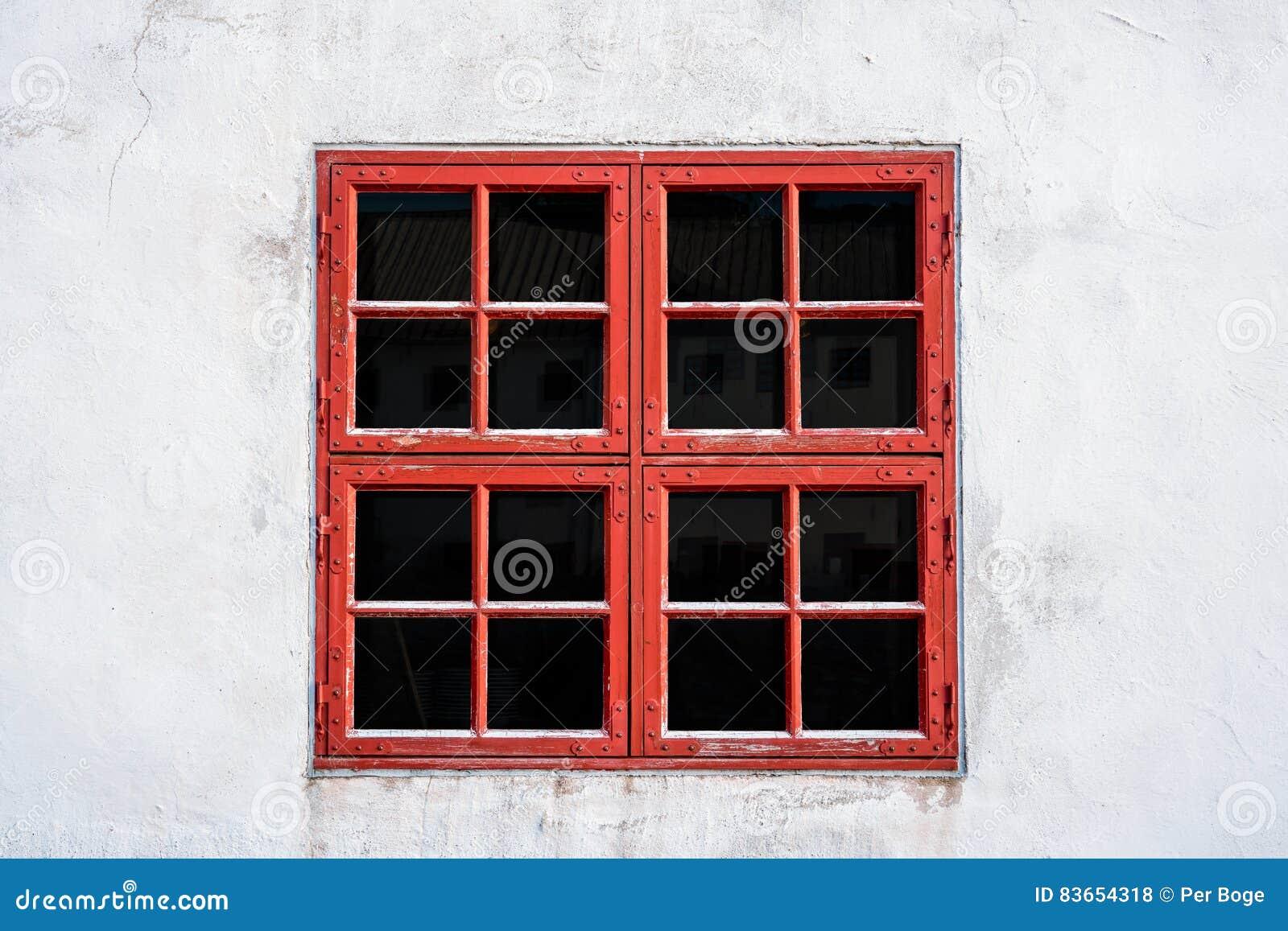 Gammalt rött ridit ut fönster med fyrkanter på den vita väggen med sliten textur